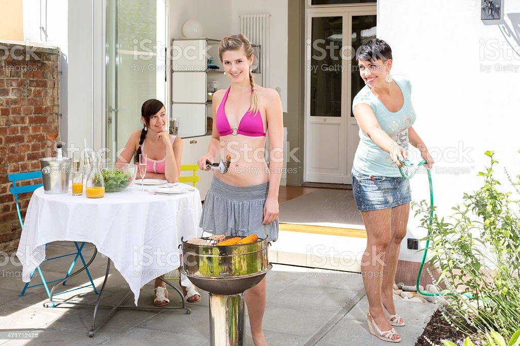 Trois femmes amis ayant barbecue sur la terrasse - Photo