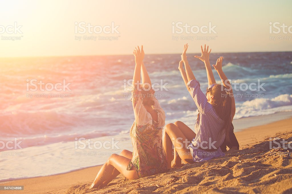 Three female friends having fun at the beach stock photo