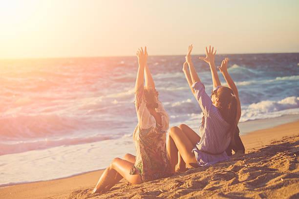 Three female friends having fun at the beach stock photo