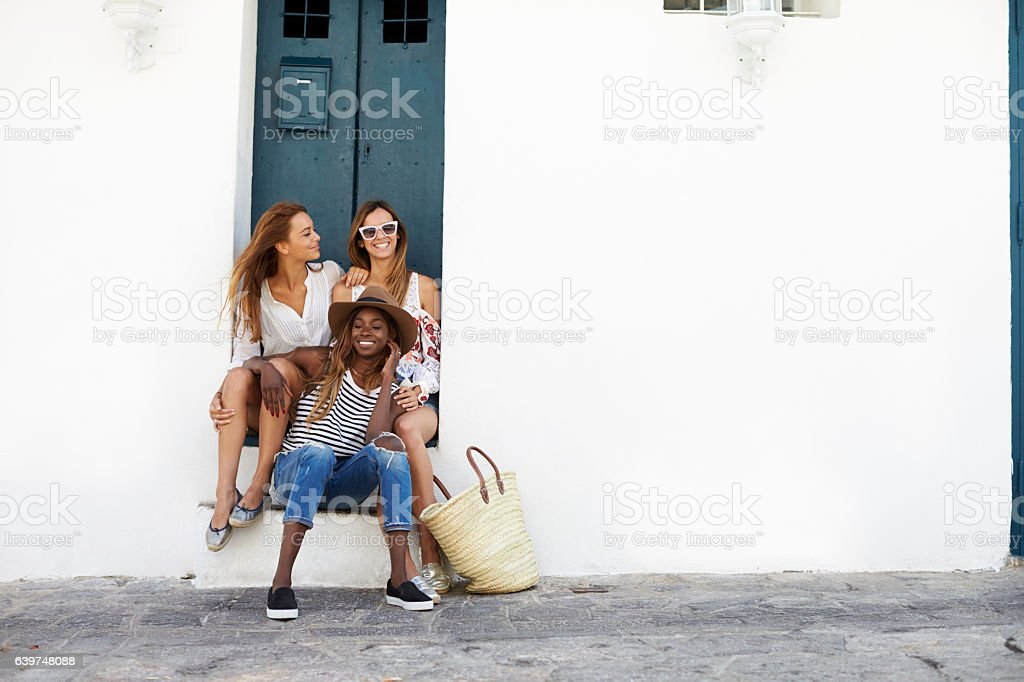 Three female friends sitting in a doorway, Ibiza stock photo