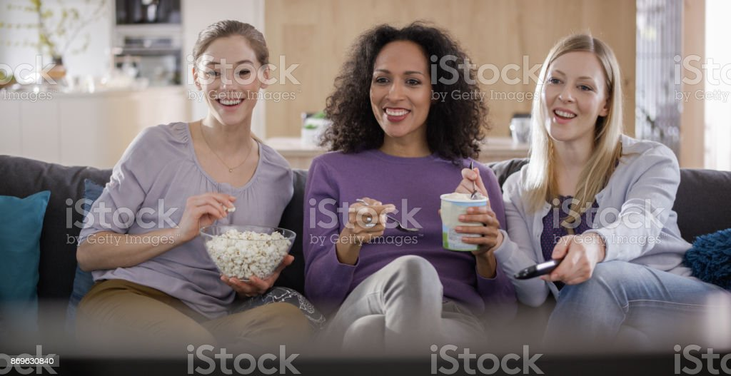 Three female friends talking while watching TV and eating popcorn stock photo