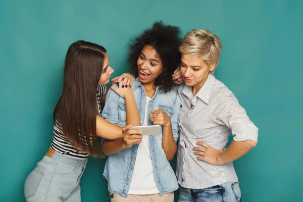 drei freundinnen, die mit smartphones - free online game stock-fotos und bilder