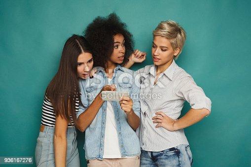 istock Three female friends using smartphones 936167276