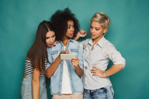 drei freundinnen, die mit smartphones - suche freundin stock-fotos und bilder
