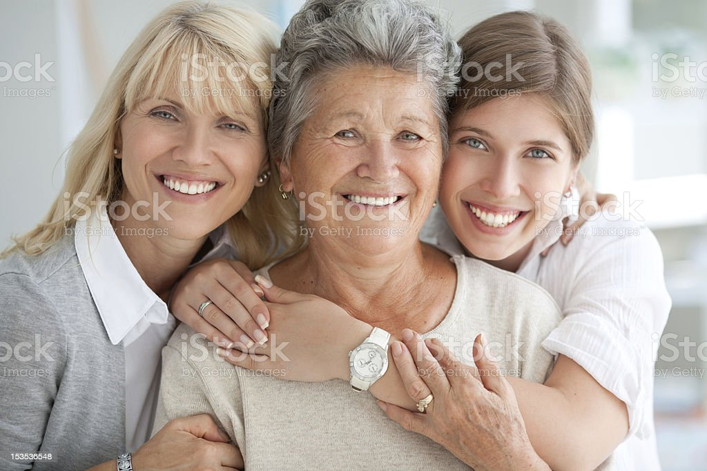 Three female generations. Three generations of woman hugging and looking at camera. 20-29 Years Stock Photo