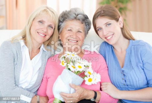 Three generations of women hugging and looking at camera.