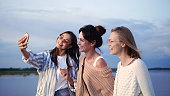 Medium shot. Slow motion.Three female models taking selfie and then looking at photos in the phone while walking. Professional shot in 4K resolution. 33. You can use it e.g. in your commercial video, medical, business, presentation, broadcast