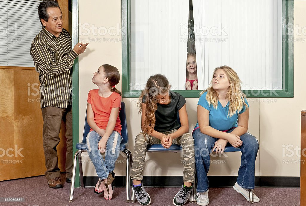 Three female students in trouble and awaiting the principal stock photo