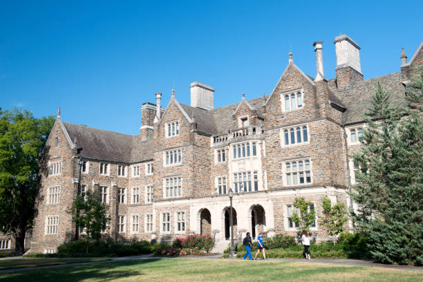 Three female students walking past a dorm building in the campus of Duke University