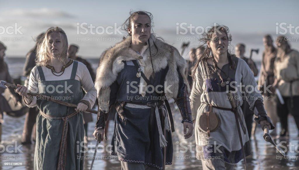 Três vikings feminino posando na frente de um grupo de guerreiros ficou no surf na costa - foto de acervo