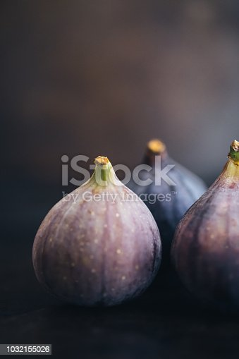 Figs are gems. Three purple figs on a table. Low light.