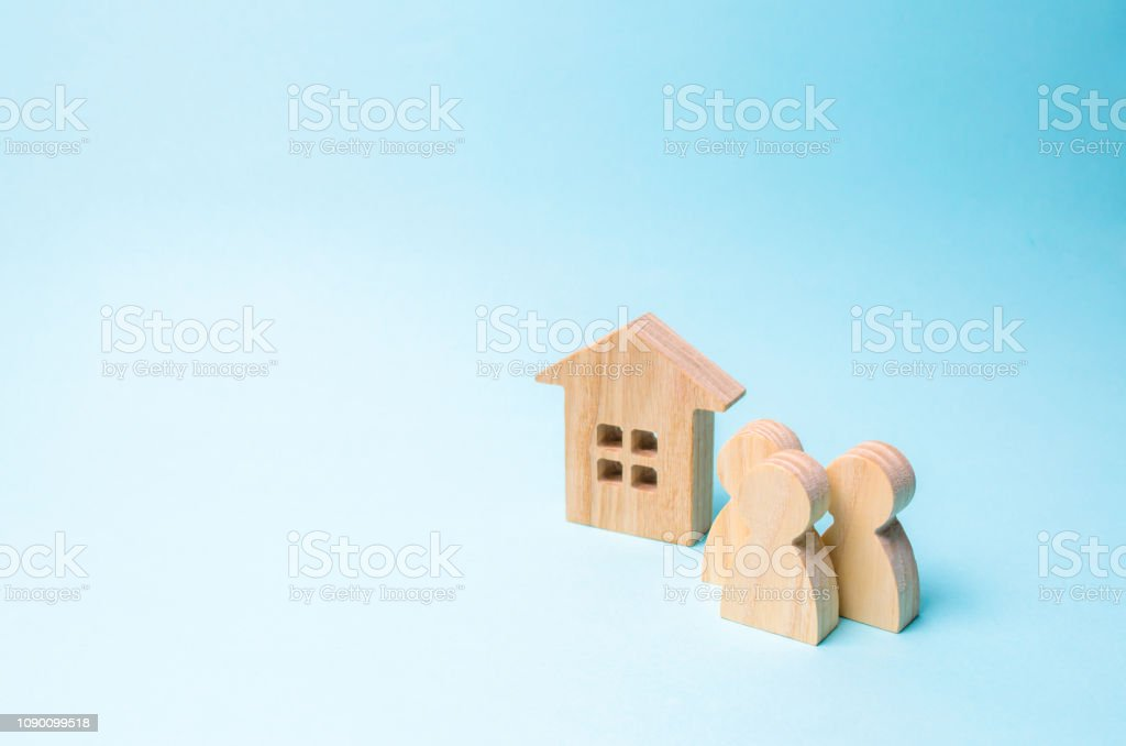 three figures of people and a wooden house on a blue background. The concept of affordable housing and mortgages for buying a home for young families and couples. Buying and selling real estate stock photo