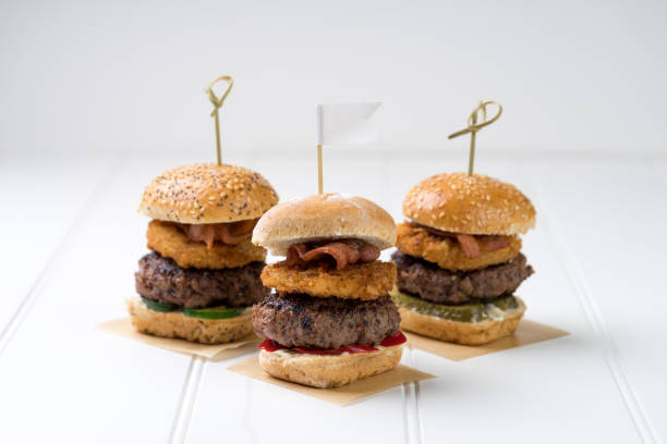 three finger food slider beef burgers for sharing Small beef sliders grilled burgers onion rings little buns bacon served as appetisers for sharing slider burger stock pictures, royalty-free photos & images