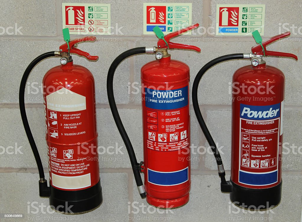 Three Fire Extinguishers stock photo