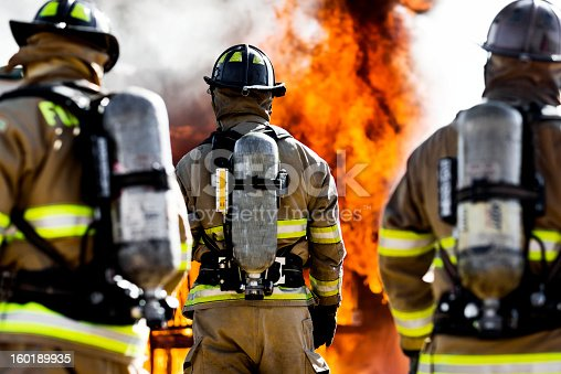 Three firefighters putting out an house fire. Horizontal shot.