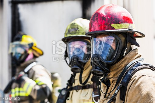 A group of three multiracial firefighters wearing protective gear, including an oxygen mask, helmets, and tan protective suit with yellow reflective stripes.  The focus is on the fireman on the right, a mixed race African American man wearing a red helmet.  The one in the background is a woman.