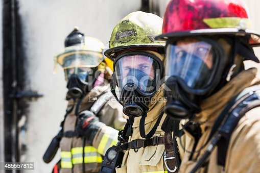 A group of three multiracial firefighters wearing protective gear, including an oxygen mask, helmets, and tan protective suit with yellow reflective stripes.  The focus is on the fireman in the middle.  The one in the background is a woman.