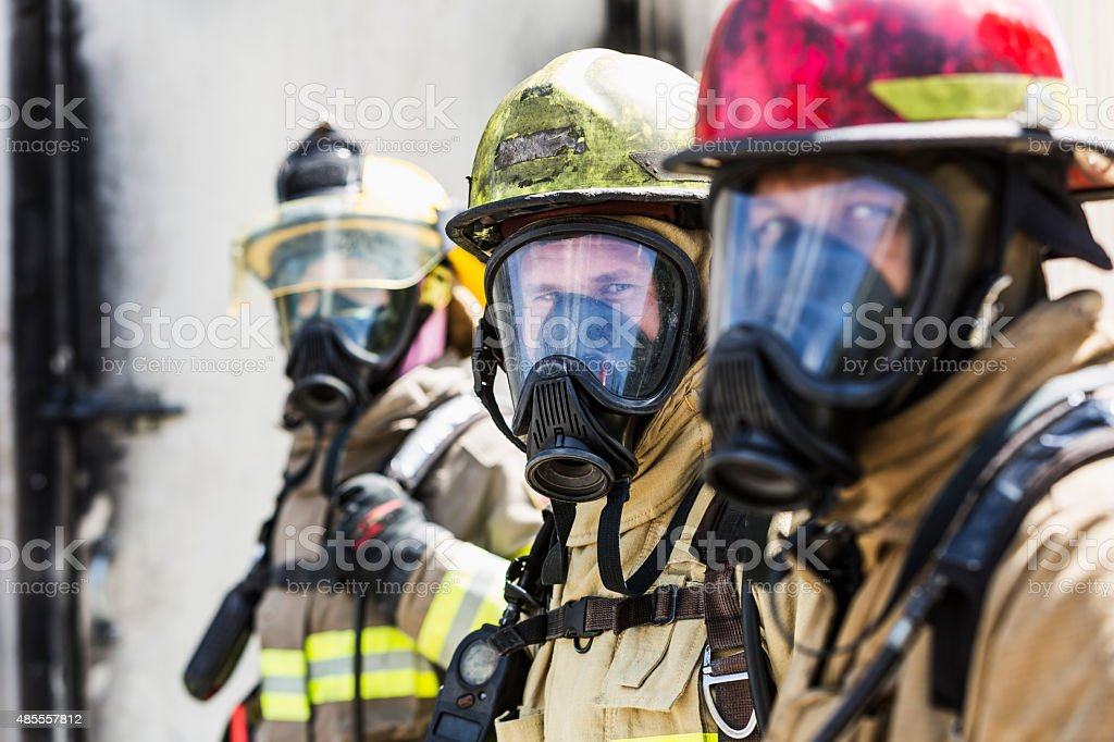 Three firefighters wearing oxygen masks stock photo