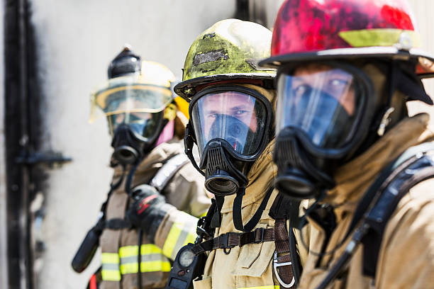 three firefighters wearing oxygen masks - firefighter stock photos and pictures