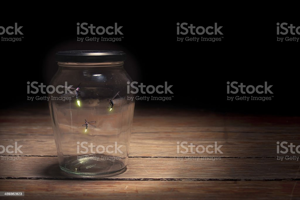 Three fireflies caught in a glass jar on wooden table stock photo