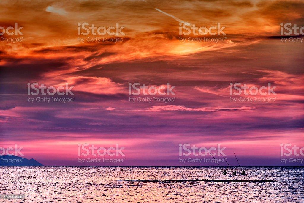 Three fishermen at sunset stock photo