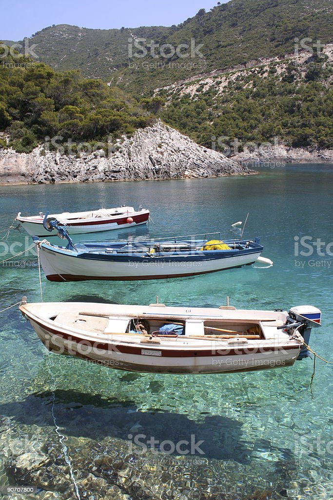 Three fishing boats resting on clear waters by the mountain stock photo