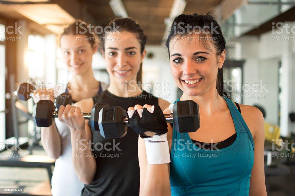 Tres en forma de mujeres jóvenes, levantamiento de pesas en el club Aptitud física. - foto de stock
