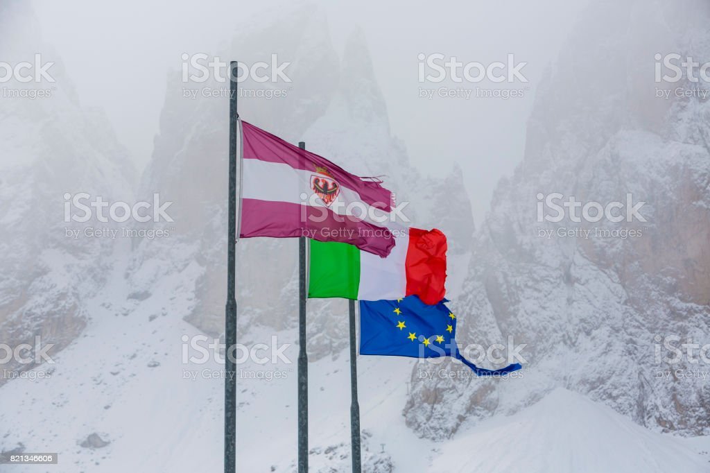 Three flags in the background mountains. Torn European Union flag on white background with mountain hill, Italy flag. stock photo