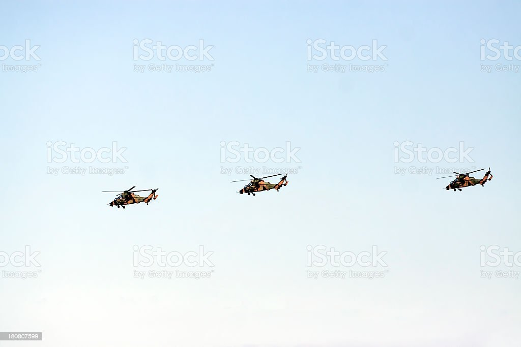 Three flying army helicopters against blue sky, copy space royalty-free stock photo