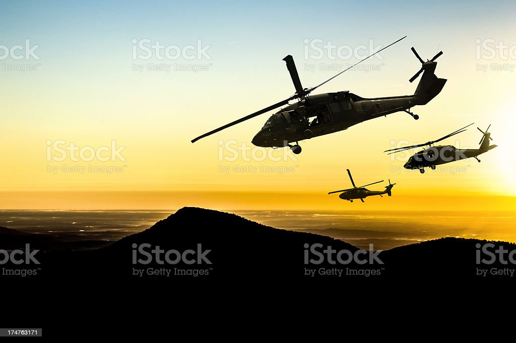 Three flying army helicopters on sunset background stock photo