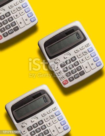 istock three flying grey big calculator on yellow background 1217112932