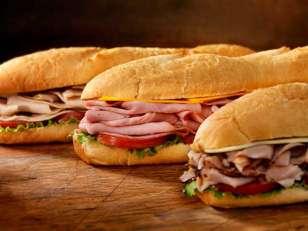 Three Foot Long Subs Three 12 inch  Submarine Sandwiches- Turkey, Ham and Cheese, Roast Beef and Swiss with Lettuce and Tomato on Crusty Buns - Photographed on Hasselblad H3D2-39mb Camera submarine sandwich stock pictures, royalty-free photos & images