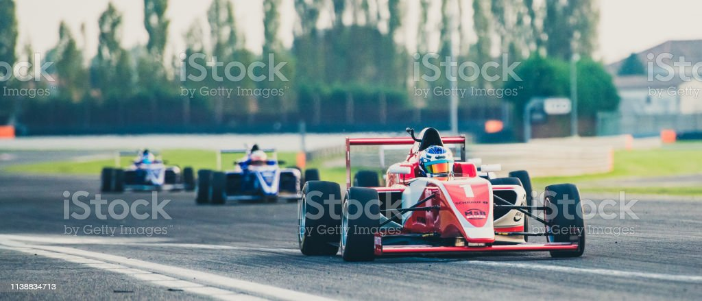 Three formula race cars on the race track Three formula race cars on the race track with a red single-seater leading the race. Auto Racing Stock Photo