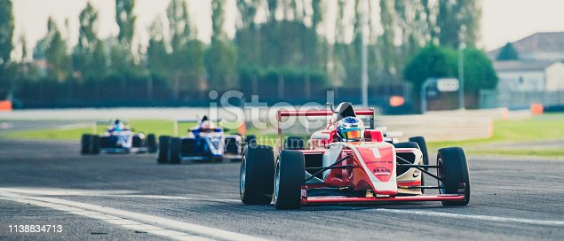 Three formula race cars on the race track with a red single-seater leading the race.