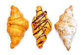 studio shot of three fresh croissants isolated on white background