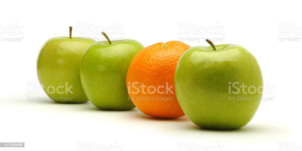 Three fresh green apples and one orange. stock photo