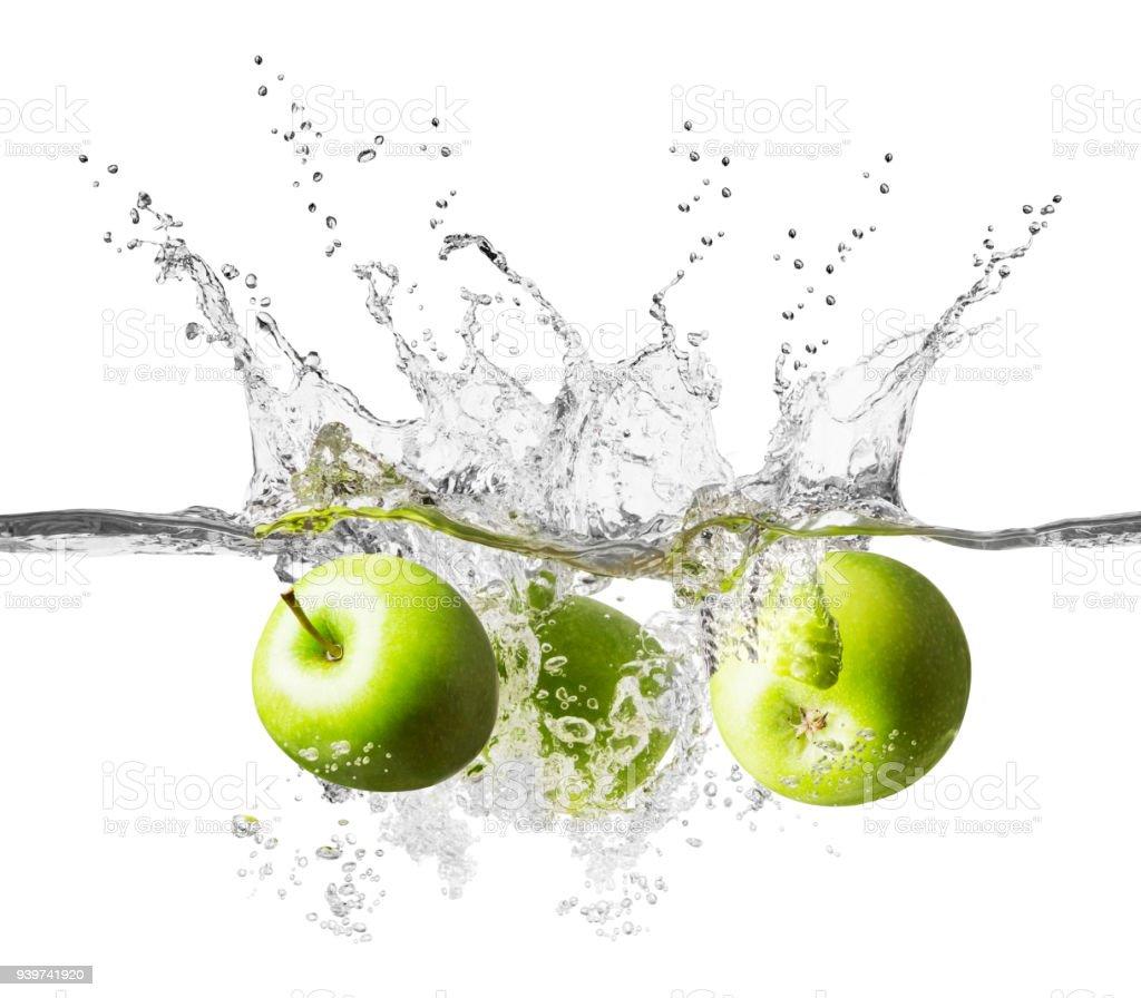 Three fresh green apples splashing into crystal clear water stock photo
