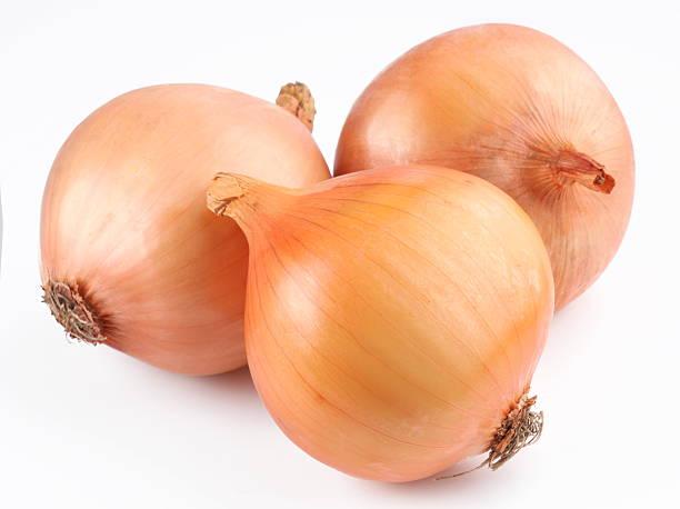 Three fresh onion bulbs on white background stock photo