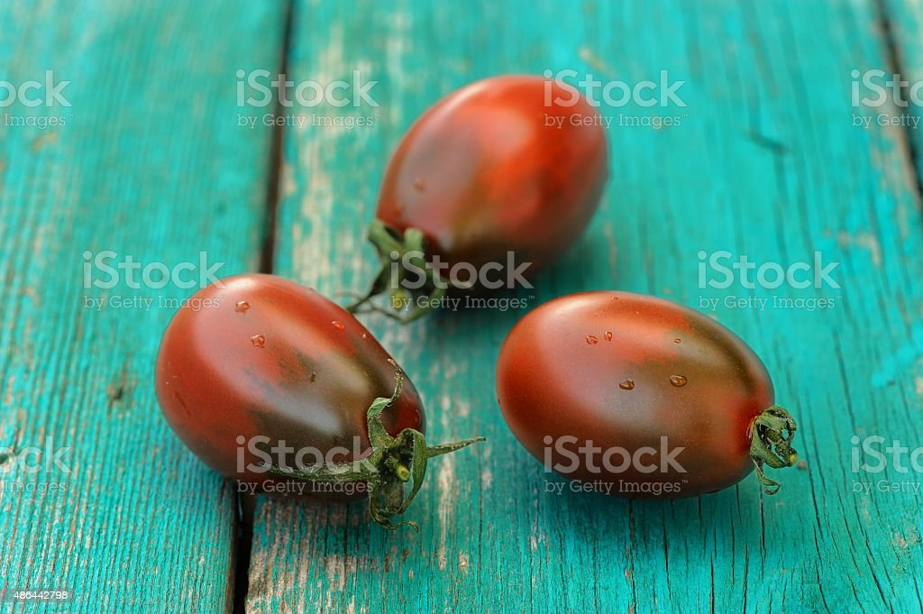 Three fresh organic red and black tomatoes on old turquoise stock photo