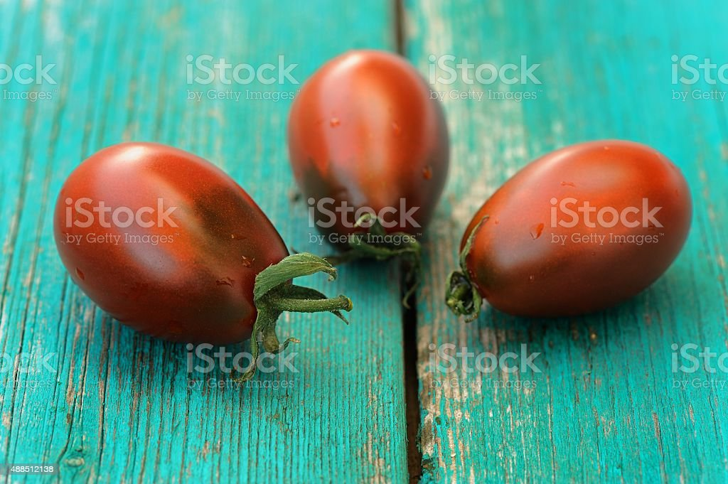 Three fresh organic red and black tomatoes on old turquoise table...