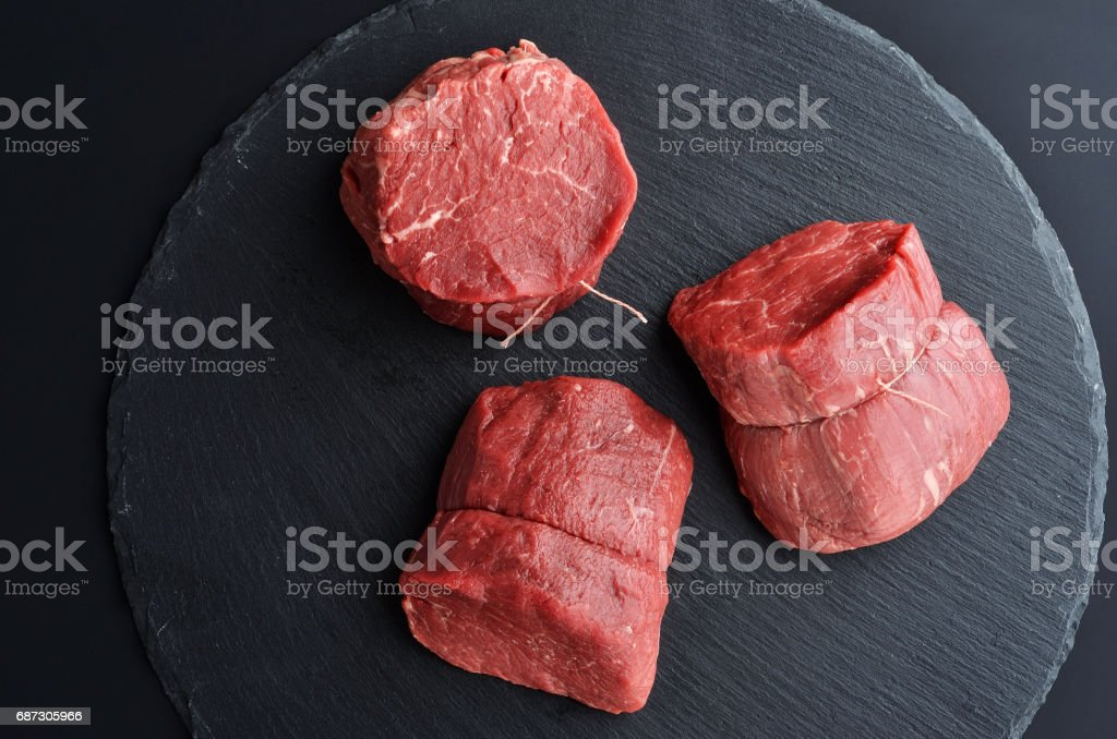 Three fresh raw Prime Black Angus beef steaks on stone background - foto de acervo