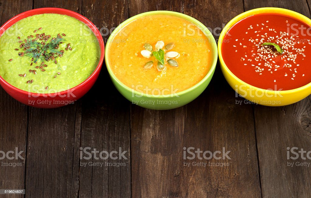 Three fresh soups on a wooden table stock photo