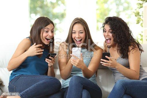 istock Three friends amazed watching a smart phone 504374602