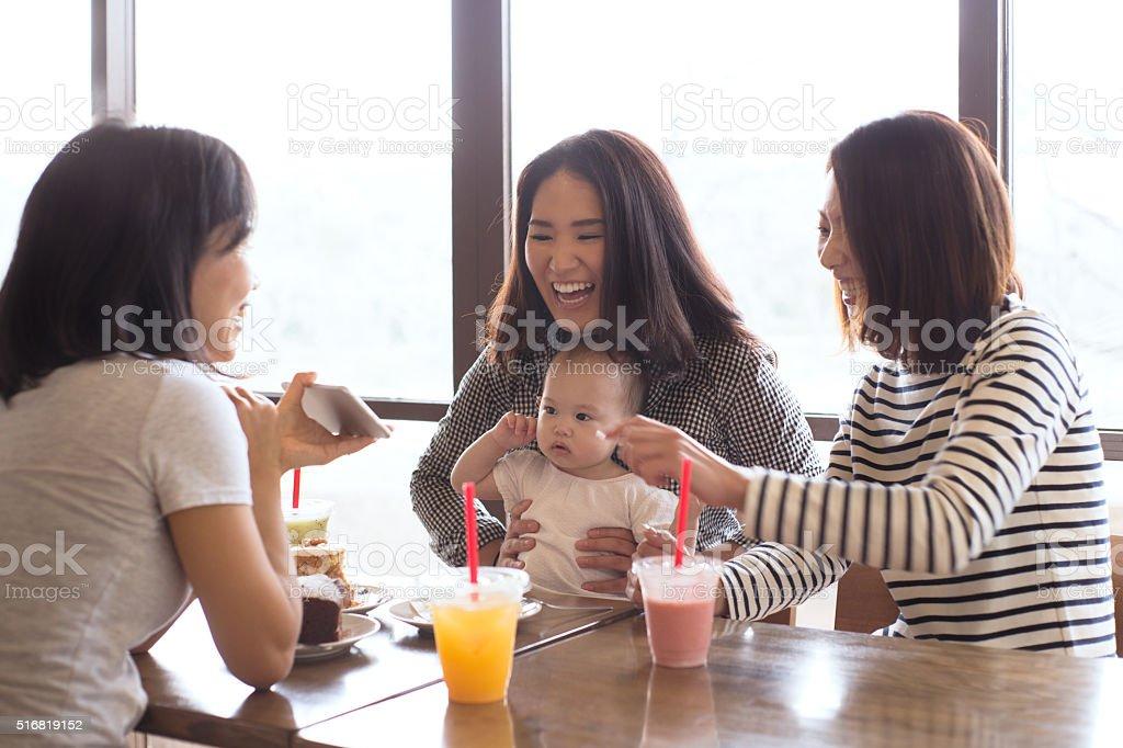 Trois amis et un bébé dans un café ensemble - Photo