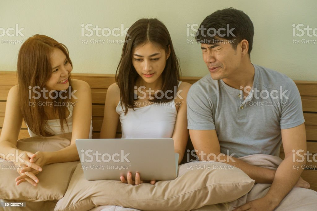 Three friends are talking. By the middle of the girl does not care, but watching the notebook in bed. royalty-free stock photo