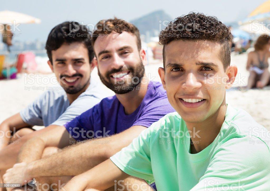Tres amigos en la playa observando un cámara - foto de stock