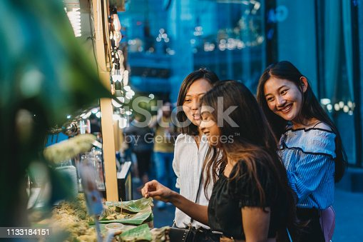 Three friends buying street food at the night market in the city