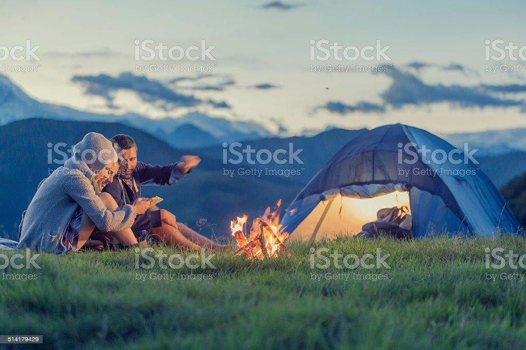 Drei Freunde camping auf die Berge bei Sonnenuntergang Lizenzfreies stock-foto