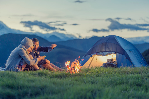 Three Friends Camping On Mountain At Sunset Stock Photo ...