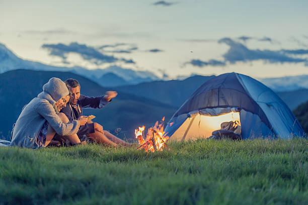 Três amigos no acampamento na montanha, ao pôr do sol - foto de acervo
